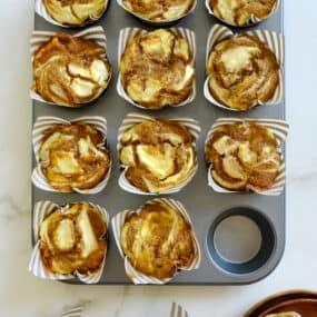 A muffin tin containing Cream Cheese Pumpkin Muffins