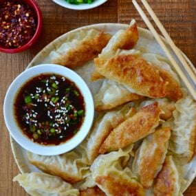Plate containing easy chicken potstickers next to small bowl with soy dipping sauce and chopsticks next to small bowls with chopped scallions and red pepper flakes