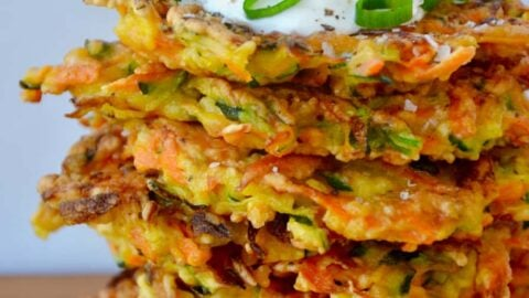 Stack of Quick and Crispy Vegetable Fritters topped with sour cream and sliced scallions
