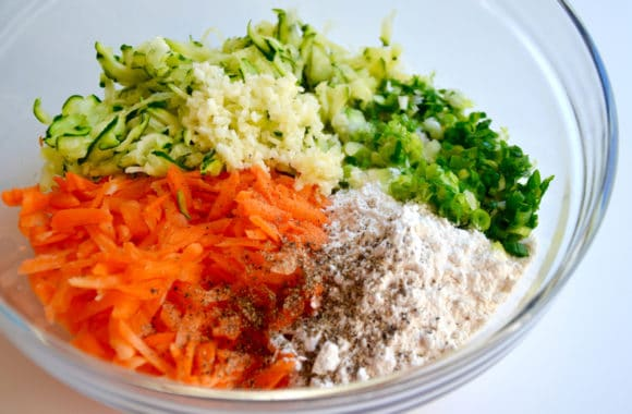 Glass bowl containing shredded zucchini, minced garlic, sliced scallions, flour, spices and shredded carrots