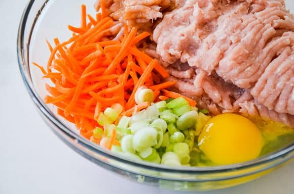 A glass bowl containing ground chicken, carrots, scallions and egg