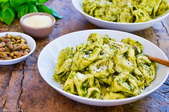Two bowls filled with Pistachio Pesto Tortellini with fresh basil in the background