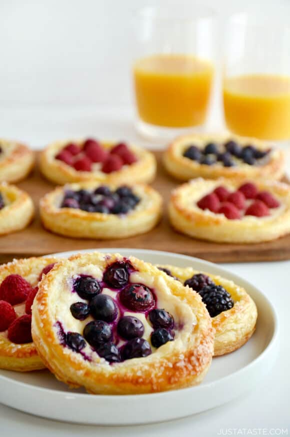 White serving plate containing Fruit and Cream Cheese Breakfast Pastries topped with blueberries with more pastries in the background topped with raspberries