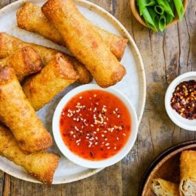 A white plate containing chicken egg rolls and a small bowl of sweet-and-sour sauce