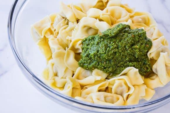 Homemade pistachio pesto atop cooked tortellini pasta