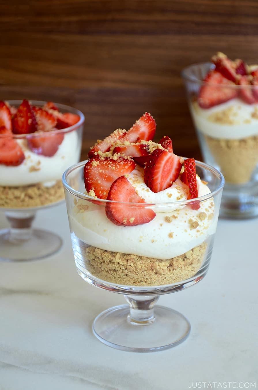 Easy No-Bake Cheesecake Parfaits in individual glasses topped with sliced fresh strawberries and graham cracker crumbles