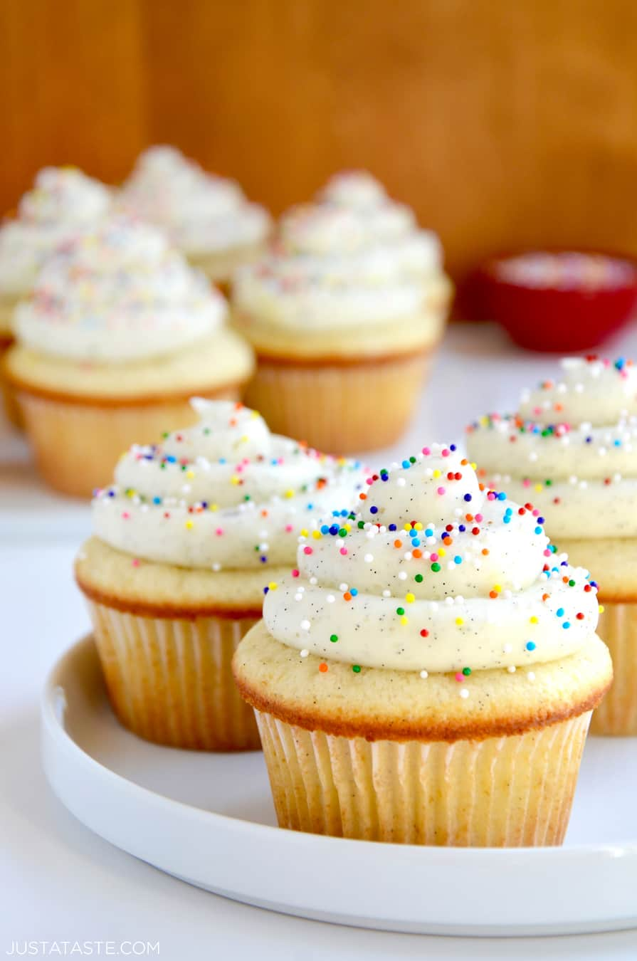 White plate containing Vanilla Bean Cupcakes with Buttercream Frosting and rainbow sprinkles