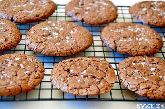 Flourless Chocolate Cookies topped with sea salt on wire cooling rack