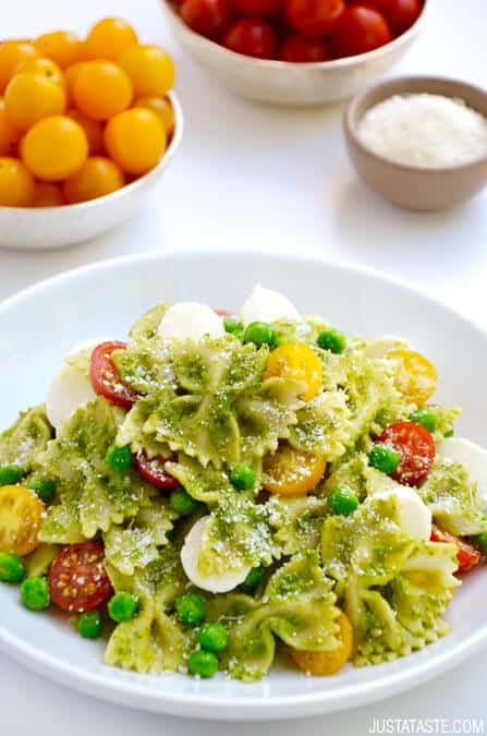 Pea Pesto Pasta Salad topped with fresh mozzarella cheese, cherry tomatoes and Parmesan cheese