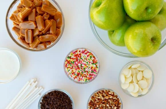 Ingredients for Easy Caramel Apples, including soft caramels, green apples, sticks, sprinkles, nuts and candy melts