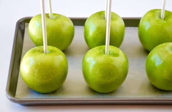 Granny Smith Apples with lollipop sticks on parchment paper-lined baking sheet