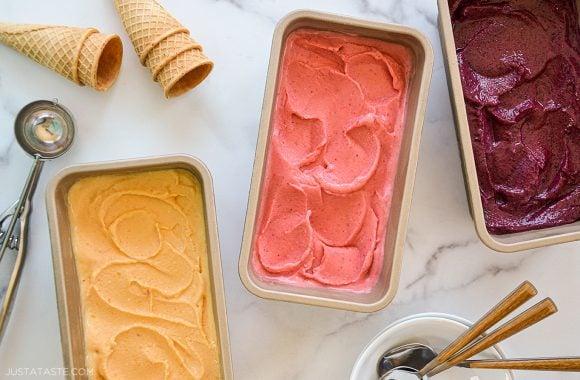 Three flavors of healthy Greek frozen yogurt with ice cream cones and a scoop