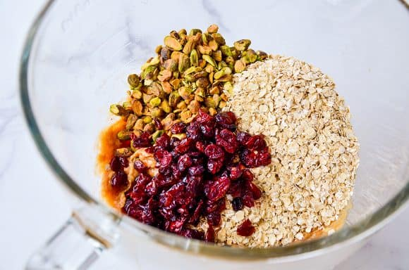 Clear mixing bowl containing quick oats, dried cranberries, pistachios and honey