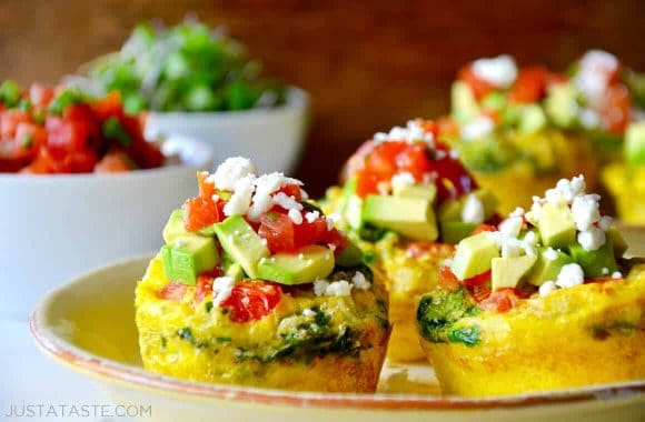 A plate containing Egg Muffins topped with avocado, salsa and cheese