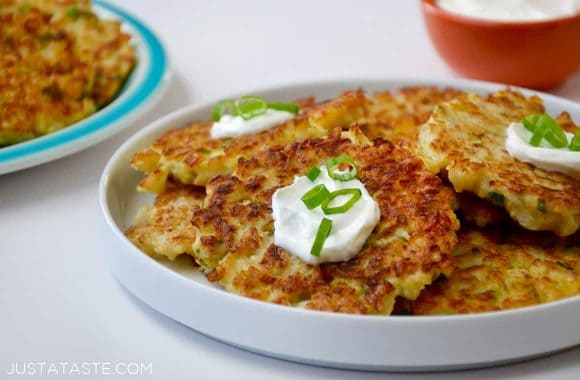 A white plate containing cauliflower fritters topped with sour cream and scallions