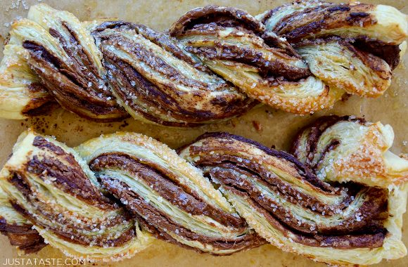 Chocolate puff pastry twists close-up on brown parchment paper