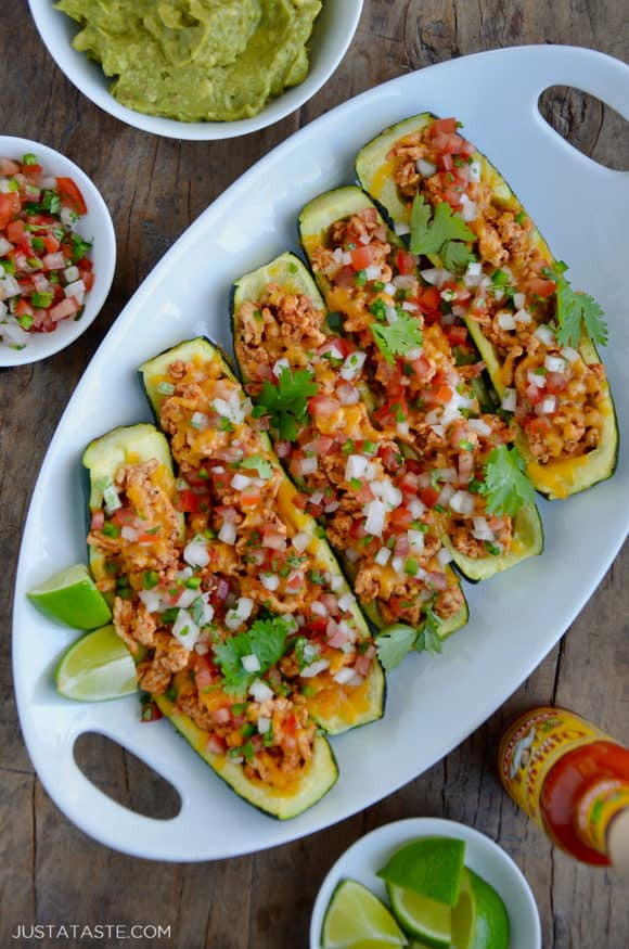 A white platter containing zucchini boats with small bowls of guacamole and salsa next to them