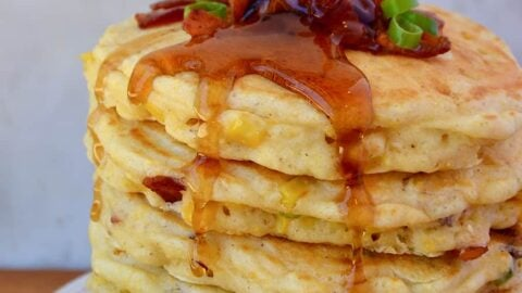 Tall stack of Sweet Corn Pancakes with Bacon topped with sliced scallions and drizzled with maple syrup