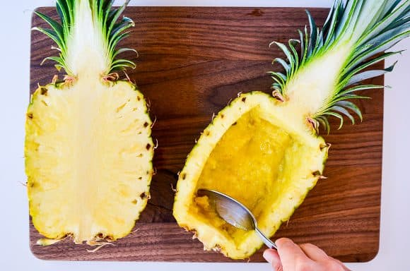 Halved pineapples being hollowed out with a spoon