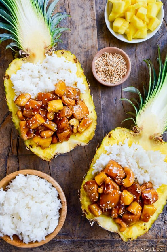 Two pineapple bowls filled with chicken and white rice