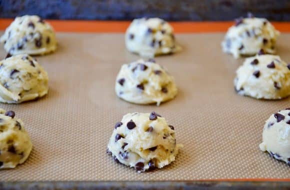 Raw cookie dough mounds on a baking sheet