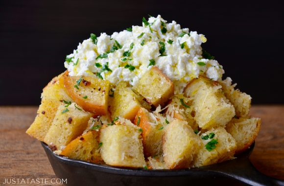 Cheesy garlic bread cubes in a skillet with ricotta cheese and herbs on top
