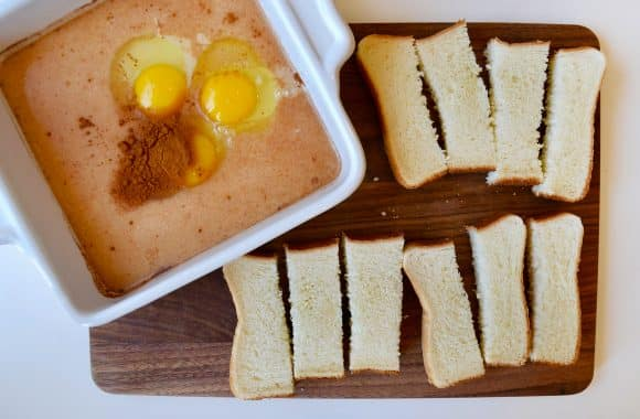 Texas toast cut into sticks alongside a dish of eggs and milk