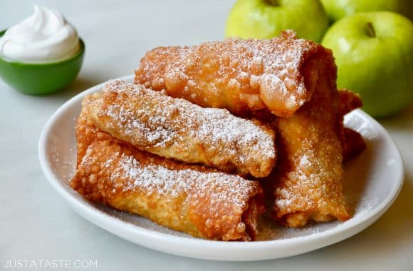 Apple pie egg rolls on a white plate dusted with powdered sugar