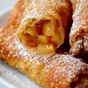 Apple pie egg rolls on a white plate with one cut open
