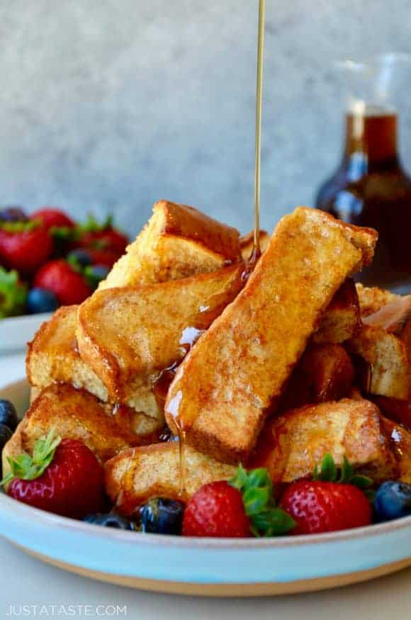 Baked French toast sticks on a plate with fruit and maple syrup being drizzled on top
