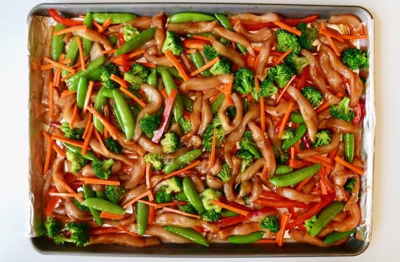 Raw chicken and vegetables arranged on a baking sheet
