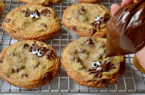 Piping chocolate spiders onto cookies