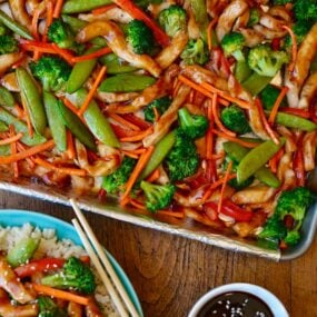 A sheet pan with chicken teriyaki and vegetable next to a plate