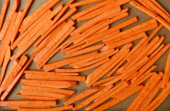 Uncooked sweet potato fries on a lined baking sheet