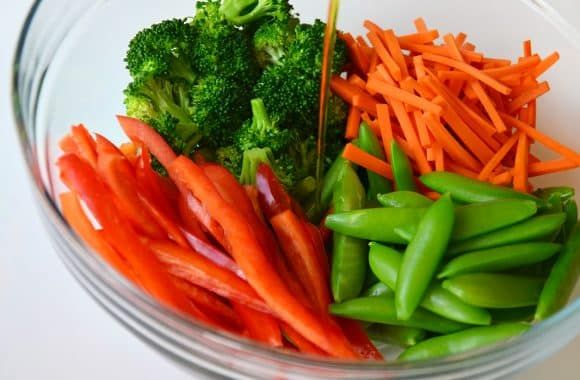 Cut vegetables in a glass bowl with teriyaki sauce on top