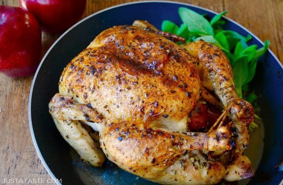 A roast chicken with apples and sage in a skillet