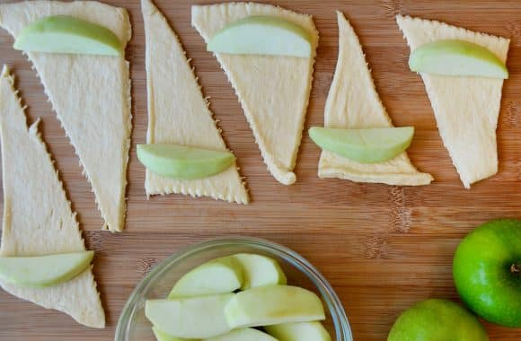 Uncooked crescent rolls and apple slices being rolled up on a cutting board