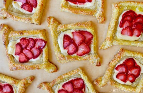 Puff pastry Danishes with cream cheese and strawberries on tan parchment paper