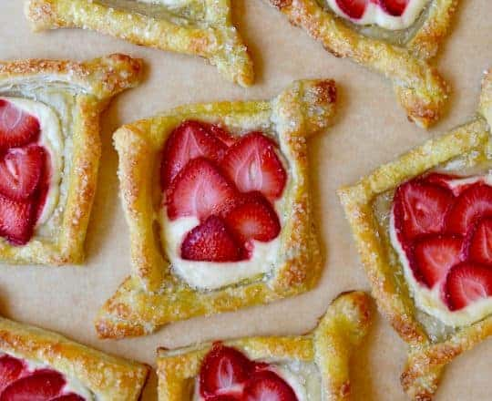 Cream cheese Danish pastries with strawberries on tan parchment paper