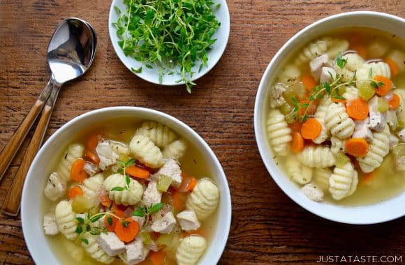 Two bowls of gnocchi chicken soup with fresh thyme
