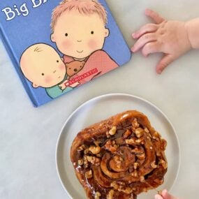 A baby's hands reaching for a sticky bun and a book