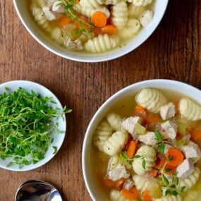 Gnocchi chicken soup in two bowls with a bowl of fresh thyme