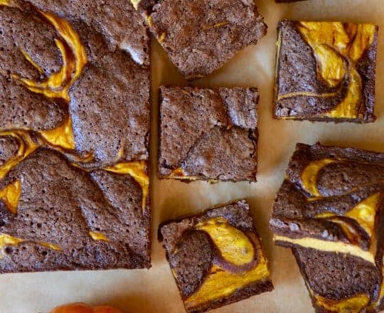 Pumpkin cheesecake brownies on tan parchment paper cut into squares with sugar pumpkins