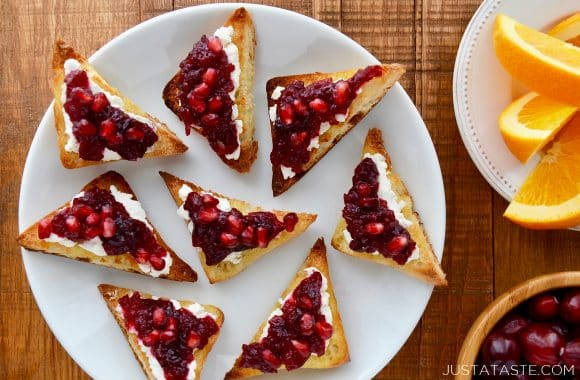 A white plate with triangular cheese toasts topped with orange cranberry relish