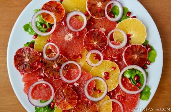 A white platter with sliced citrus fruits and honey dressing