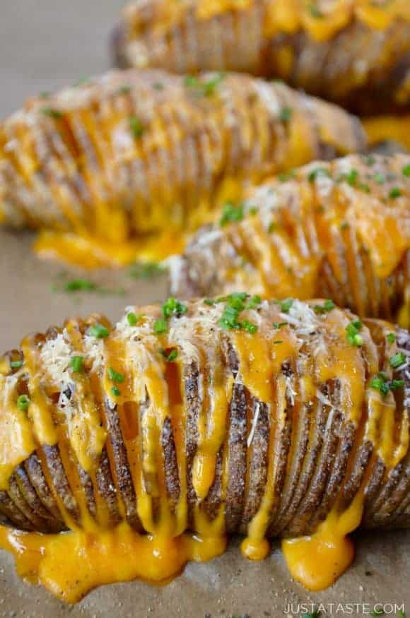 Hasselback potatoes filled with cheese on a baking sheet