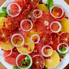 A white plate containing sliced citrus fruits and red onions