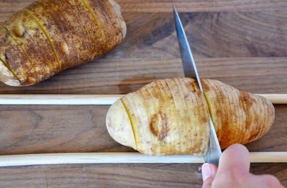 Cutting hasselback potatoes on a cutting board