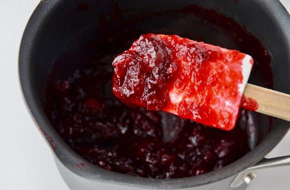 A white spatula containing orange cranberry relish over a saucepot