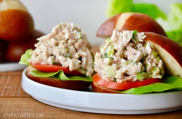 A white plate with Leftover Turkey Sliders on pretzel buns with lettuce and tomato